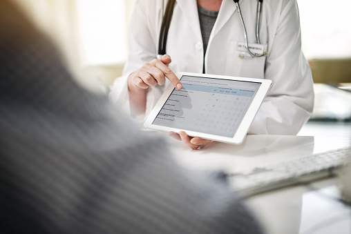 Assistant  showing patient online forms on a digital tablet